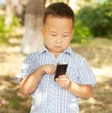 Aziatische jongen 6 jaar oud met een mobiele telefoon in een park Royalty-vrije Stock Fotografie