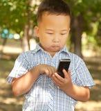 Aziatische jongen 6 jaar oud met een mobiele telefoon in een park Stock Fotografie