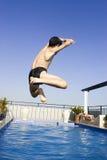 Aziatische jongen jumpin in zwembad Stock Afbeeldingen
