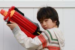 Aziatische jongen met een stuk speelgoed kanon Stock Foto's