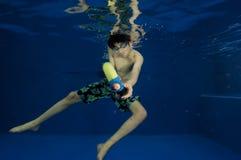 Aziatische jongen met straalkanon onder water stock afbeelding
