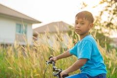 Aziatische jongens berijdende fiets in openbaar park Royalty-vrije Stock Foto's