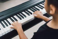 Aziatische jongens die de piano spelen Stock Foto
