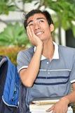 Aziatische Jongensstudent Wondering With Books stock afbeeldingen