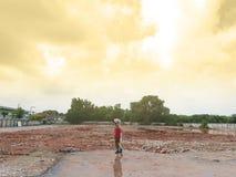 Aziatische jongenstribune alleen op het de bouwgebied van de vernielingswoestenij in de zonsondergangtijd met raylight en bewolkt stock foto