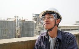 Aziatische kerel die een helm dragen die in een grote industriële fabriek werken die het productieproces controleren stock foto's