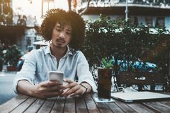 Aziatische kerel in straatkoffie met laptop en cocktail stock foto