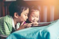 Aziatische kinderen die op video en speelspel op digitale tablet letten stock foto's