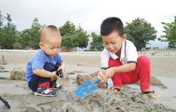 Aziatische kinderen die zand spelen Royalty-vrije Stock Afbeelding