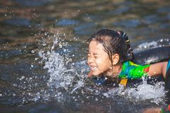 Aziatische kindmeisjes die water met opblaasbare ring in de rivier in de zomertijd met pret en geluk spelen royalty-vrije stock fotografie