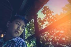 Aziatische kindzitting dichtbij venster en het kijken opzij terwijl droevig het voelen stock afbeelding