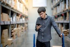 Aziatische klant die het winkelen lijst in pakhuis controleren stock afbeelding