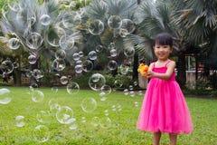Aziatische Kleine Chinese Meisjes die Bellen van Bellenventilator schieten royalty-vrije stock afbeelding