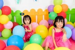 Aziatische Kleine Chinese Meisjes die met Kleurrijke Ballons spelen Royalty-vrije Stock Afbeeldingen