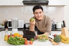 Aziatische knappe mens die thuis recept op laptop in keuken kijken royalty-vrije stock afbeelding