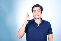 Aziatische knappe mens met de sleutels van zijn nieuwe auto, op blauwe backgro Stock Afbeeldingen