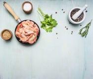 Aziatische kokende ingrediënten met verse kleine garnalen in een kleine pan, kruiden en peper, houten blauwe achtergrond hoogste  Royalty-vrije Stock Fotografie