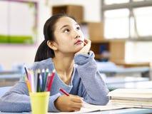 Aziatische lage schoolstudent die in klaslokaal denken stock foto's
