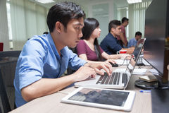 Aziatische Laptop van Zakenmansitting at desk Werkende Computerzaken Stock Fotografie