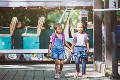 Aziatische leerlingsjonge geitjes met de hand van de rugzakholding en het gaan naar school royalty-vrije stock foto
