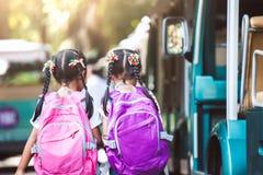 Aziatische leerlingsjonge geitjes met de hand van de rugzakholding en het gaan naar school stock foto's