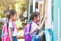 Aziatische leerlingsjonge geitjes met de hand van de rugzakholding en het gaan naar school stock afbeeldingen