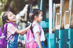 Aziatische leerlingsjonge geitjes met de hand van de rugzakholding en het gaan naar school stock afbeelding