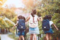 Aziatische leerlingsjonge geitjes met rugzak die naar school gaan Royalty-vrije Stock Foto