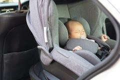 Aziatische leuke slaap van de maand de oude pasgeboren baby in moderne autooverzees Royalty-vrije Stock Afbeeldingen