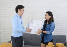 Aziatische leveringsmens die doos geven aan aantrekkelijk meisje stock afbeeldingen