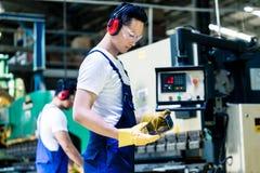 Aziatische machineexploitant in productie-installatie stock afbeelding