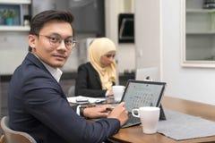 Aziatische malay mens die thuis met laptop met collega bij achtergrond werken royalty-vrije stock fotografie