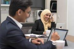Aziatische malay moslim die hijab het werken thuis met laptop met collega draagt bij voorgrond stock fotografie