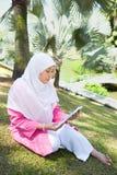 Aziatische Maleise Moslimvrouwenlezing Stock Afbeeldingen