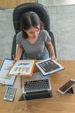 Aziatische manager die verkooprapporten in haar bedrijfsbureau controleren royalty-vrije stock fotografie