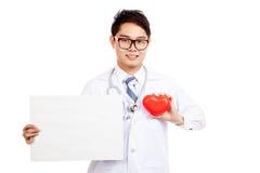 Aziatische mannelijke arts met rood hart over borst en leeg teken Stock Afbeelding
