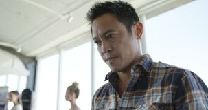 Aziatische mannelijke directeur die mobiele telefoon in modern bureau 4k met behulp van stock video