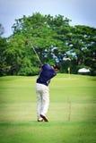 Aziatische Mannelijke golfspeler op de cursus van het Golf Stock Afbeelding