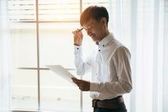 Aziatische mannelijke van de bedrijfs zakenmanlezing contractdocumenten in privé werkruimte stock fotografie
