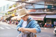 Aziatische mannelijke verstoorde reiziger Verloor binnen één of ander belangrijk dingsconcept stock foto