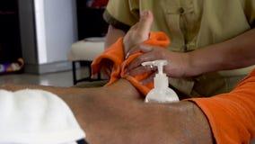 Aziatische massagist die voetmassage voor mannelijke benen doen stock video