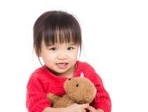 Aziatische meisjeomhelzing met pop Stock Afbeelding