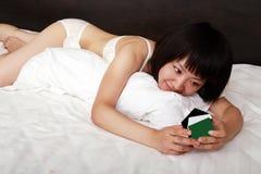 Aziatische meisjes die op bed liggen Stock Fotografie