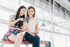 Aziatische meisjes die smartphone gebruiken die vlucht of online controle bij luchthaven samen, met bagage controleren Luchtreis, stock foto