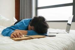 Aziatische meisjesslaap op bed na het werken en het schrijven stock foto's