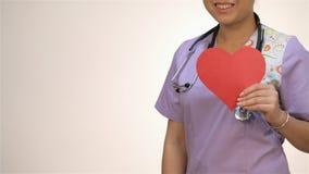 Aziatische meisjesverpleegsters die een document hart houden stock videobeelden