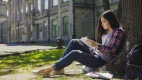 Aziatische meisjeszitting onder boom, die schets van omgeving in notitieboekje, kunstenaar maken royalty-vrije stock foto's