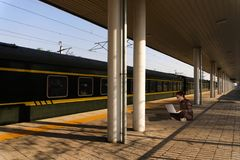 Aziatische meisjeszitting op het spoorwegplatform royalty-vrije stock fotografie