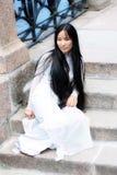 Aziatische meisjeszitting op steendijk Stock Afbeelding