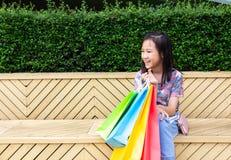 Aziatische meisjeszitting openlucht met het winkelen zakken stock afbeelding